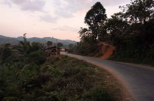 Small villages cling to Highway 1 as it winds through the mountains of Northern Laos, trucks and buses sound their horns to warn villagers to clear the road of children and livestock - Andy Scott/ASIA BRIEFING