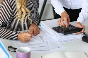 Two female accountants counting on calculator income for tax form completion hands closeup. Internal Revenue Service inspector checking financial document. Planning budget audit concept
